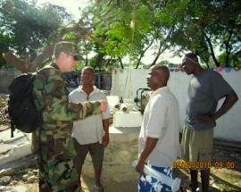 LCDR Russell assists well pump trouble shooting at a Grand Goave IDP Camp