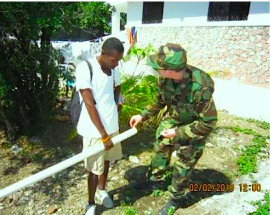 LCDR Russell explains the assembly of a well drop-pipe at a Grand Goave IDP camp