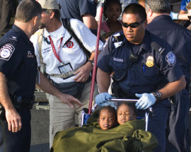 DHS Customs and Border Protection officer pushing 2 Haitian orphans in a wheelchair