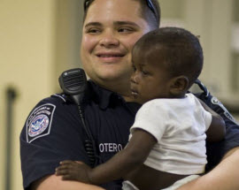 DHS Customs and Border Protection officer holding Haitian child