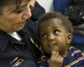 Haitian child eating and looking at a DHS Customs and Border Patrol officer