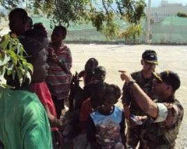 Captain Belardo and Commander Denis performing needs assessment with Haitian children.