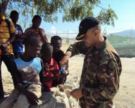 Captain Belardo performing needs assessment with Haitian children.