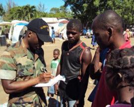 Lieutenant Commander Jean Paul gathering intelligence from young Haitian men.