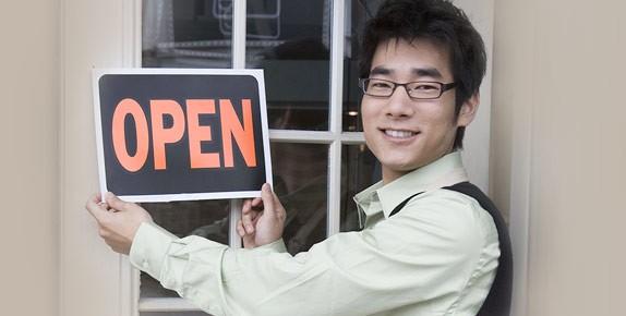 Asian businessman hanging Open sign