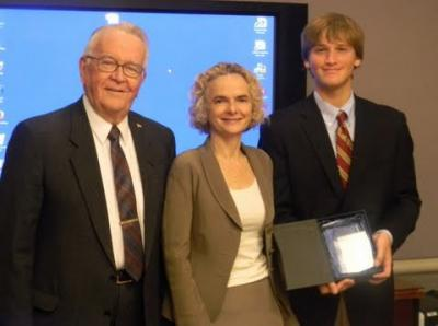 A man and a women presenting an award to a young man.
