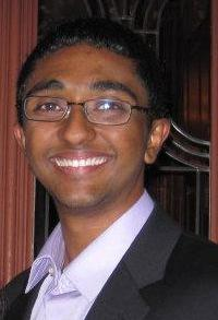 A young man smiling, with glasses.