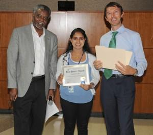 Two adults presenting and award to a teenage girl.