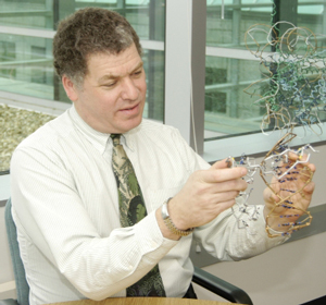 NIGMS Director Dr. Jeremy M. Berg uses wire models he constructed to show how a zinc finger protein fits into the major groove of double-helical DNA