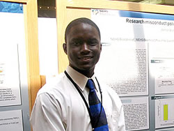 2008 intern Winnon Brunson standing in front of research poster on research misconduct policies of scientific journals