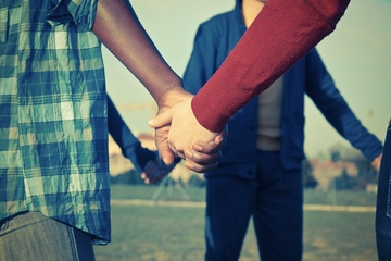 A group of young people holds hands.
