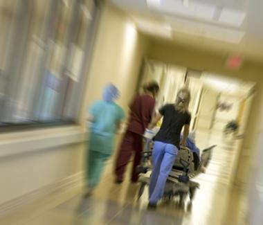 Nurses bringing patient down hospital hall