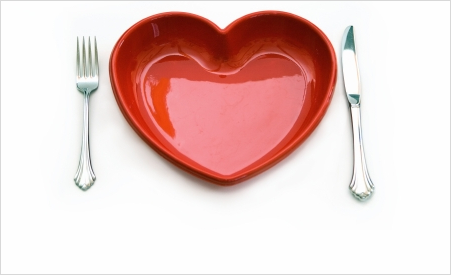 red, heart-shaped dinner plate with fork and knife