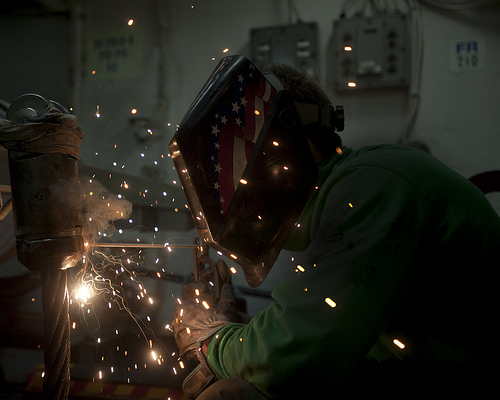 Image description: U.S. Navy Aviation Boatswain's Mate Equipment 3rd Class Devin McMaster welds an anchor terminal on an arresting gear cable aboard the aircraft carrier USS George Washington in the Pacific Ocean. Photo by U.S. NavyMass Communication Specialist 3rd Class William Pittman