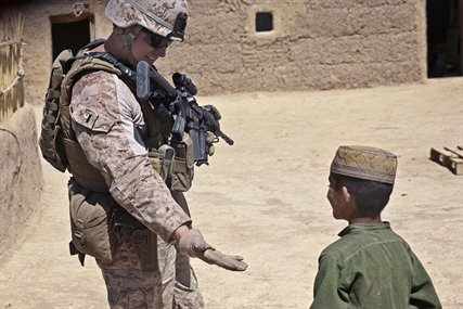 U.S. Marine Corps 1st Lt. Michael Smith interacts with an Afghan boy in Barrmo in the Washir district of Afghanistan, Sept. 19, 2013. Smith is assigned to the 33rd Georgian Liaison Team.